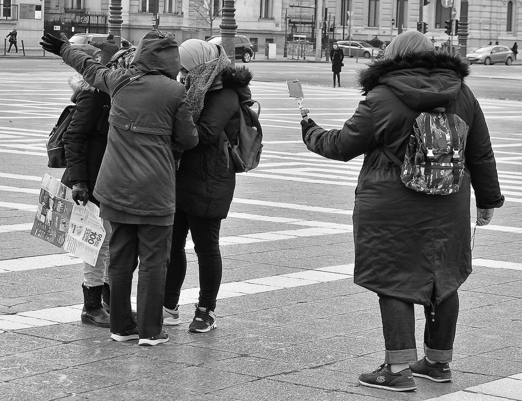 Heroes' Square képe. heroessquare hosöktere budapest hungary woman men people rucksack mobilephone coat hood car pedestrians road traffic trafficlights bollards square lampposts gate selfiestick pest urban nikon d5200 1855mm bw mono monochrome blackandwhite streetphotography street